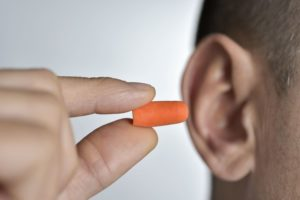man putting on an earplug